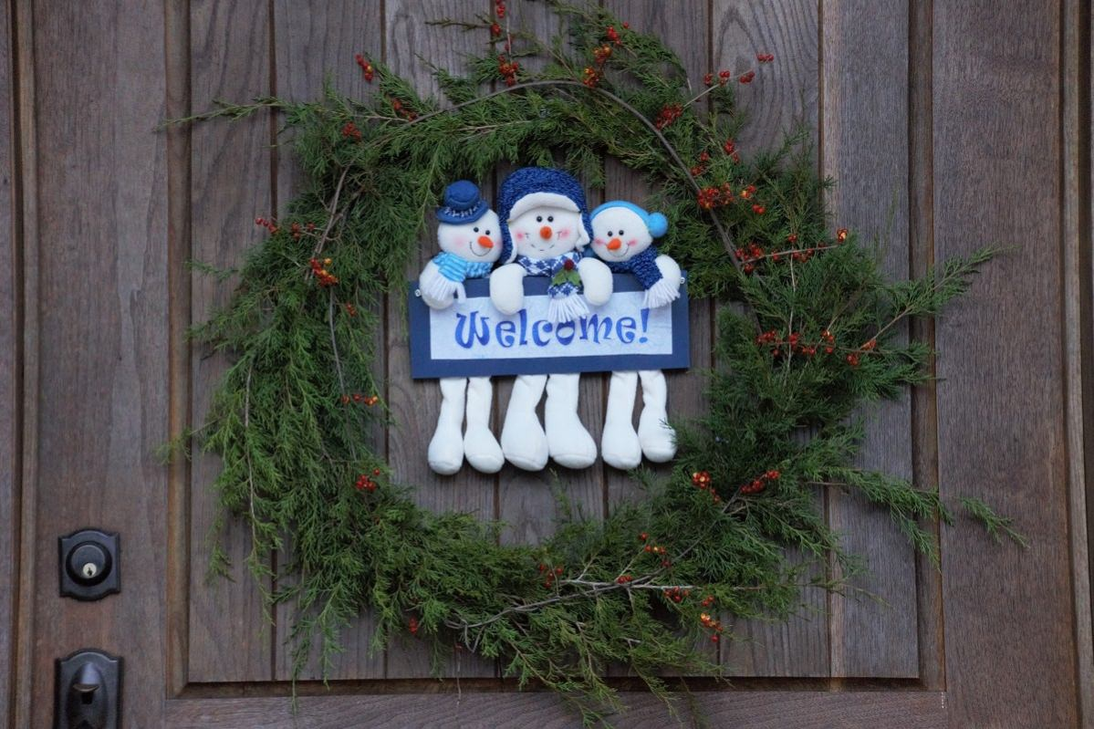 Green cedar bough wreath with snowmen welcome sign in the middle