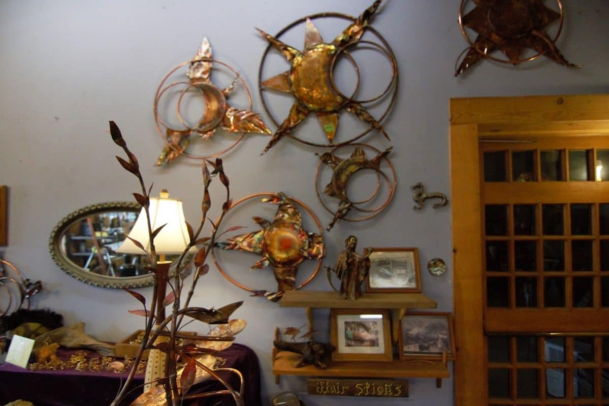Copper sculptures hanging on the wall inside the Rainmakers Shop